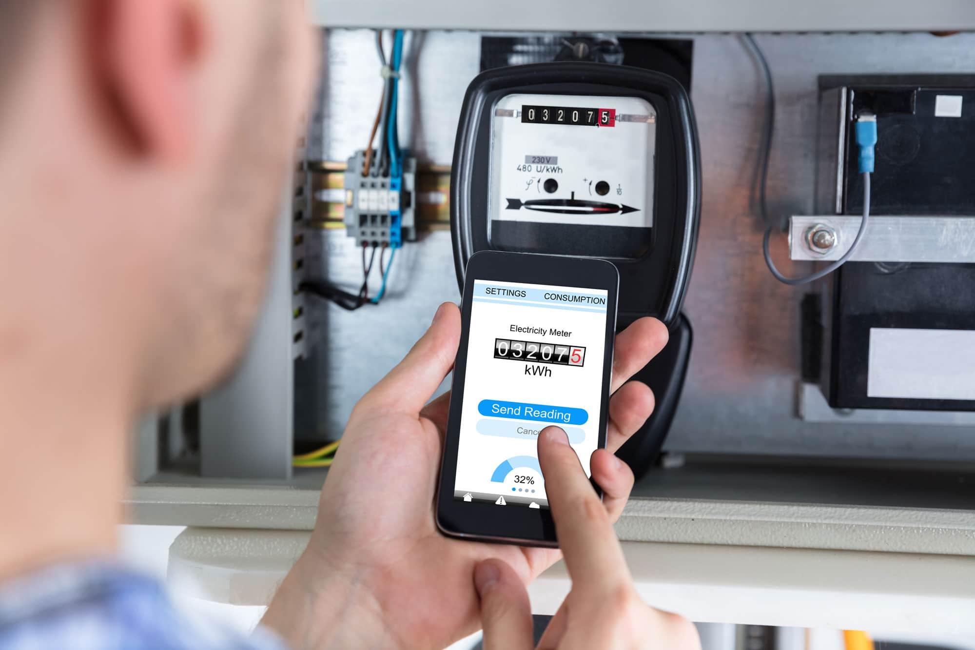 man taking meter reading at electrical box