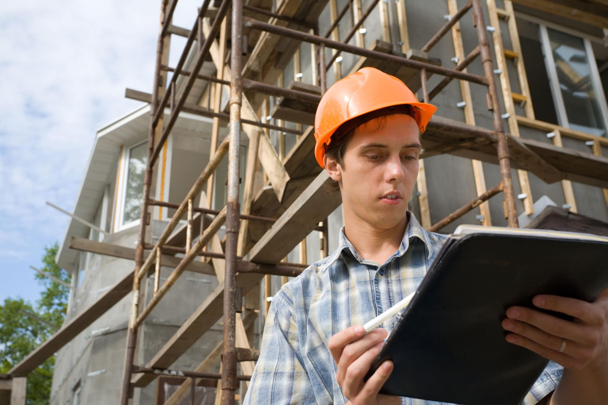 Young man in hard hat looking at clipboard at construction site