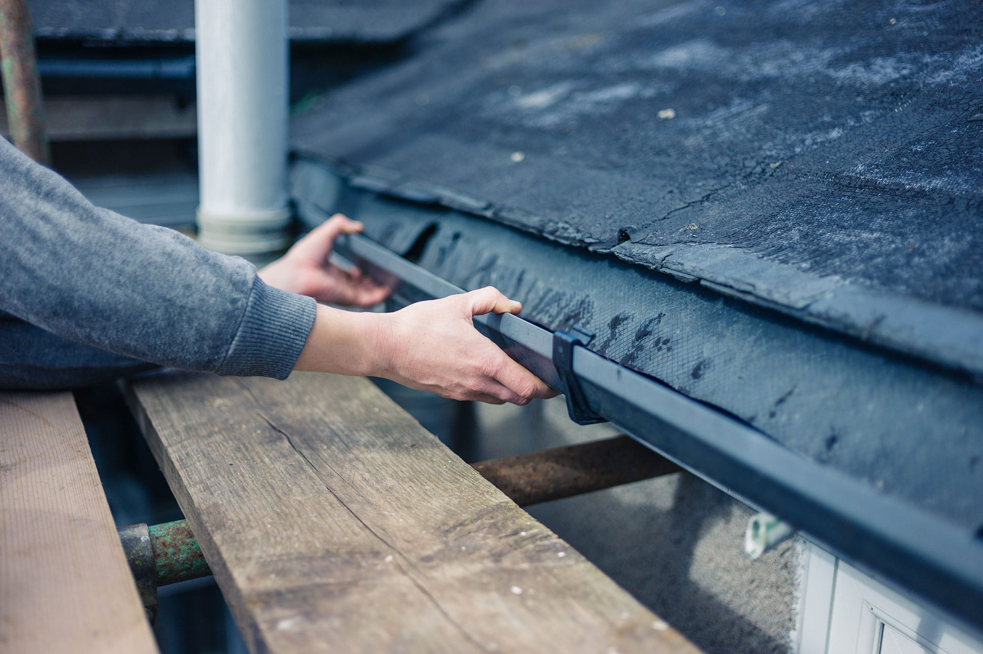 Hands adjusting gutter on roof
