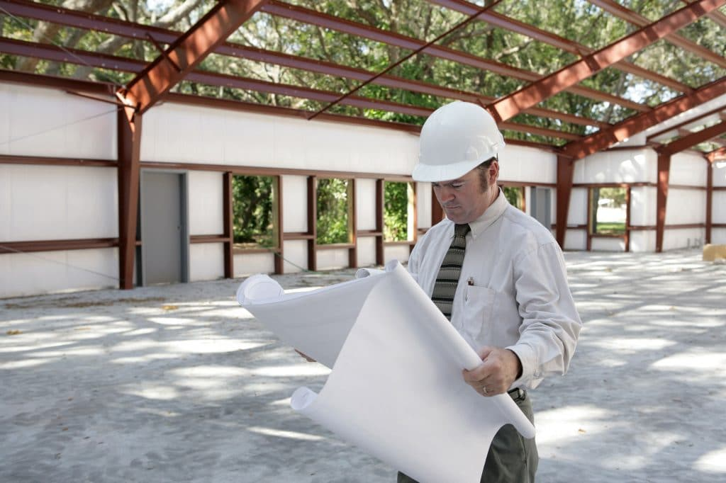 Man in hard hat examining blueprints at construction site